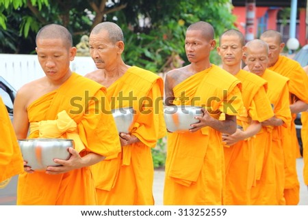 Chonburi, THAILAND - September 05 2015: Buddhist give food offerings to a Buddhist monk in morning at Nuchanard village road Thailand - stock photo