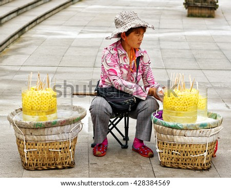 CHONGQING, CHINA â?? April 13, 2106: Female Chinese street vendor selling fresh pineapple in the Peoples Square in Chinese city of Chongqing. Street food is offered at many places throughout the city - stock photo