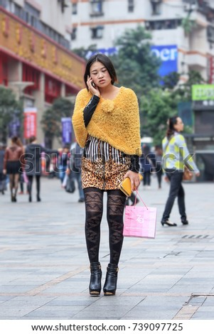CHONGQING-NOV. 4, 2014. Fancy girl in shopping area with mobile phone. The number of mobile phone users reached 1.306 billion at December 2015 according Ministry of Industry and Technology of China.
