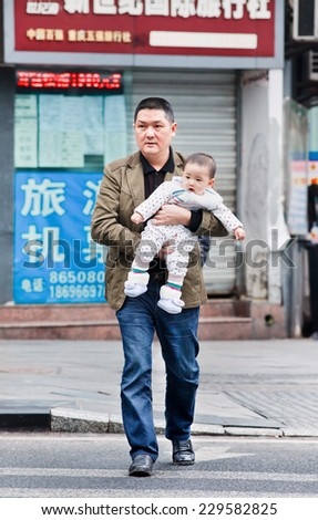 CHONGQING-NOV. 4, 2014. Father carry his young son. After 30 years of Chin's one child policy, many families won't take advantage of allowing a second child because of rising cost of child-rearing.  - stock photo