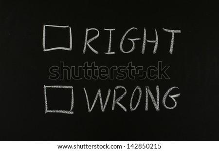 choose right or wrong?written on blackboard - stock photo