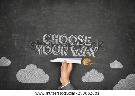 Choose your way concept on black blackboard with businessman hand holding paper plane - stock photo