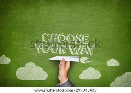 Choose your way concept on green blackboard with businessman hand holding paper plane - stock photo
