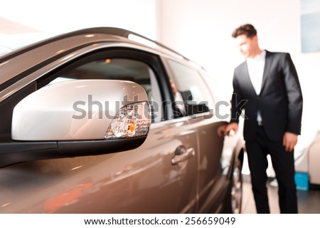Choosing a car at dealership. Thoughtful young business man in formalwear standing beside the car and looking away with selective focus - stock photo