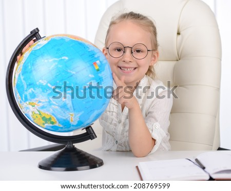 Choosing a traveling point. Cheerful little girl in formalwear examining globe while sitting at the table - stock photo