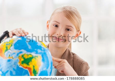 Choosing a traveling point. Cheerful little girl in formalwear examining globe with a loupe while sitting at the table - stock photo