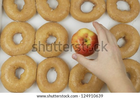 Choosing An Apple Instead Of Donuts - stock photo