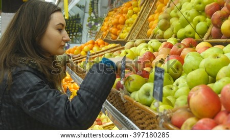 Choosing and buying apples at the store  - stock photo