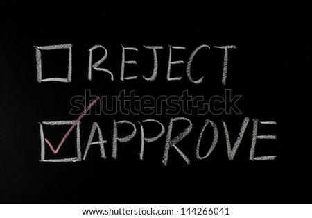 choosing approve with chalk on blackboard - stock photo