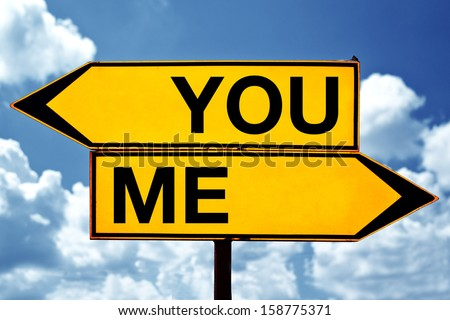 Choosing between You and me. Two opposite signs against blue sky background. - stock photo