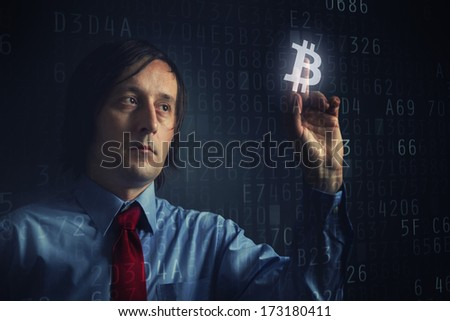 Choosing bitcoins as currency, businessman pressing touch screen button. - stock photo