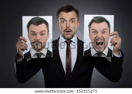 Choosing mask on today. Surprised young man in formalwear holding two photographs of himself expessing different emotions while isolated on grey - stock photo