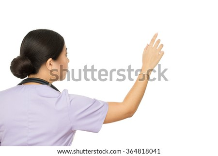 Choosing newest medicine. Female doctor pointing on a copyspace on the wall isolated on white - stock photo