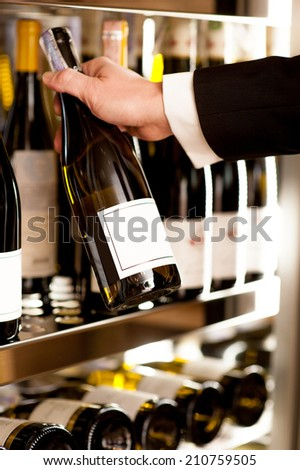 Choosing the best wine. Close-up of man in formalwear choosing wine from a shelf - stock photo