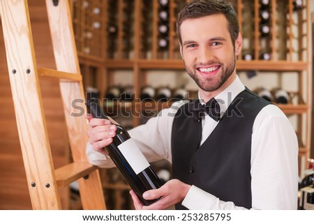 Choosing the best wine for you. Confident young man in waistcoat and bow tie holding bottle with wine and smiling while standing in liquor store  - stock photo
