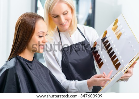 Choosing the color. Stylist is helping her customer to choose the most perfect hair tint. - stock photo