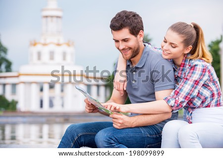 Choosing the place to go next. Happy young tourist couple sitting near beautiful building and examining map together - stock photo