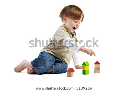 Choosing the right house. Cute little boy pointing to one of three wooden houses. - stock photo