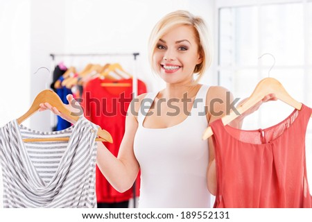 Choosing what to wear. Beautiful young blond hair woman holding two dresses and looking at camera - stock photo