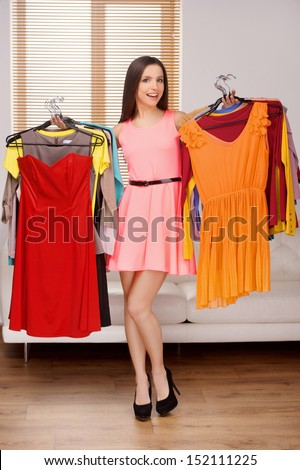 Choosing what to wear. Full length of beautiful young woman holding dresses in her hands and smiling at camera - stock photo