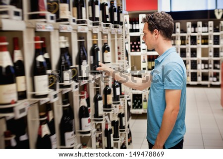choosing wine in the shop - stock photo