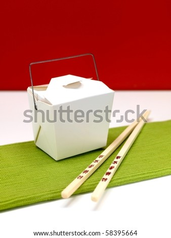 Chop sticks and a takeaway box on a kitchen bench - stock photo