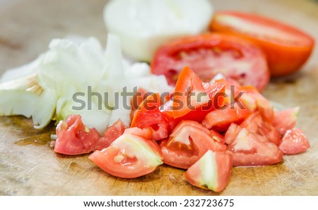 Chop tomato and onion on chopping wood - stock photo