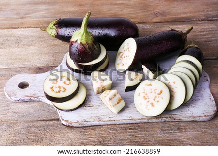 Chopped aubergines on cutting board on wooden background - stock photo