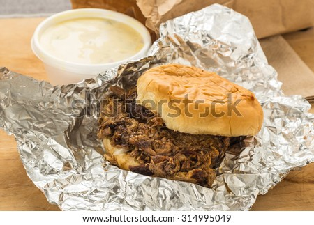 Chopped Barbecue Beef Brisket on bun wrapped in aluminum foil with brown paper bag and order of potato salad. - stock photo