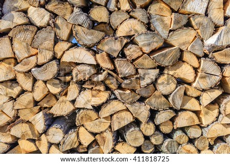 Chopped brown firewood, stacked and ready for winter. Stack of wood detailed background photo texture. - stock photo