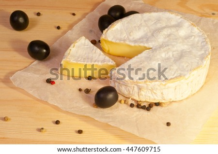 Chopped Camembert cheese and olives on the paper