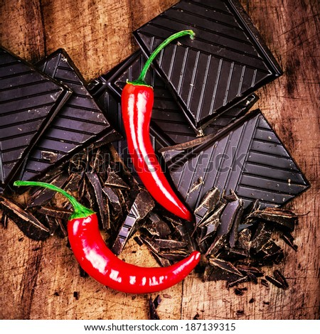Chopped Chocolate Bar with Red Chilli Pepper on wooden background closeup. Chunks of Broken dark chocolate bar on wood table macro. - stock photo
