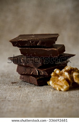 Chopped chocolate with several wallnuts on cotton map - stock photo