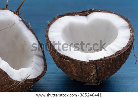 Chopped coconut: coconut halves in the shape of a heart on a blue background - stock photo