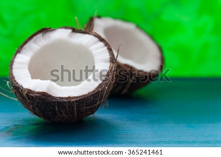 Chopped coconut: coconut halves on a blue background - stock photo