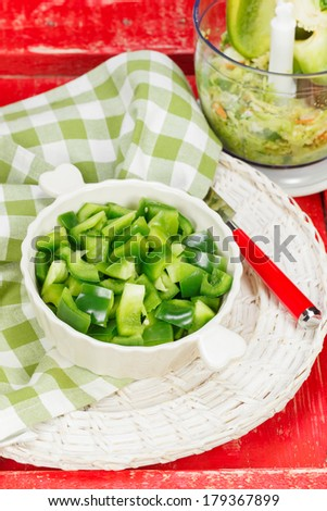 Chopped Green Bell Pepper in bowl and food  processor on table. Macro, selective focus. - stock photo