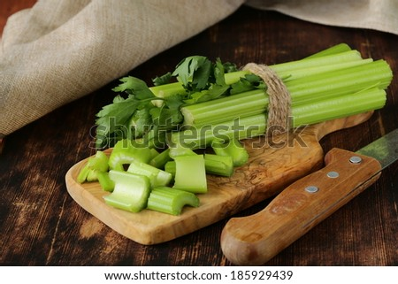 chopped green celery on a kitchen wooden board - stock photo