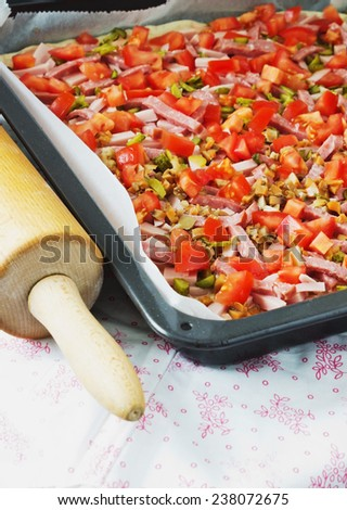 chopped ingredients for pizza on a baking sheet for baking at the kitchen table - stock photo