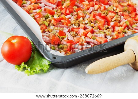 chopped ingredients for the pie in the pan for baking at the kitchen table. meat and vegetable pie - stock photo
