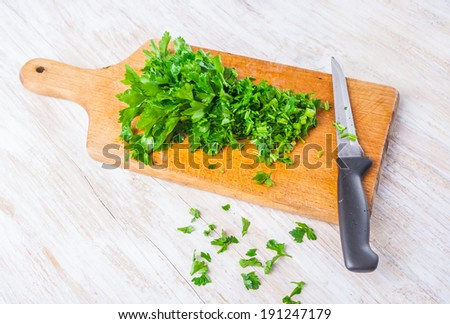 chopped parsley leaf on a wooden table - stock photo