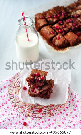 Chopped pieces of dessert brownie on an openwork stand with a bottle of milk