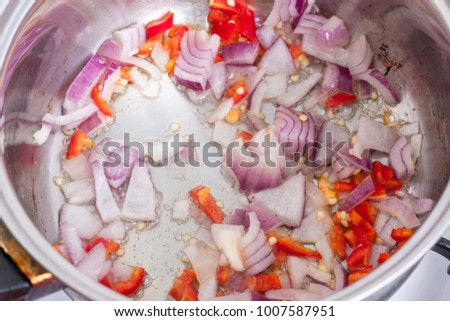 Chopped red onion and chilli frying in oil in a saucepan