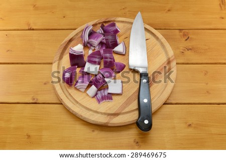 Chopped red onion with a sharp kitchen knife on a chopping board on a wooden table - stock photo