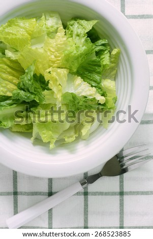 Chopped romaine lettuce in white bowl with fork in vertical format - stock photo