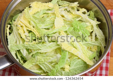 Chopped savoy cabbage in stainless steel saucepan.