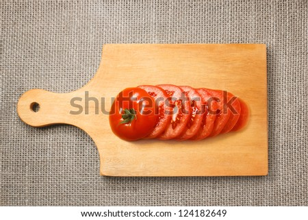 Chopped tomato on wooden cutting board with sacking background