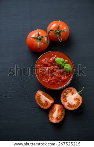 Chopped tomatoes over black wooden background, view from above - stock photo