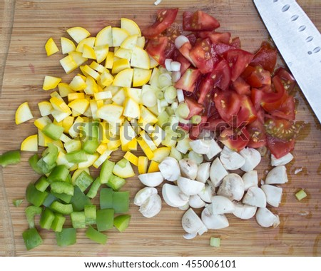 Chopped up tomatoes, summer squash, mushrooms and peppers over a cutting board.