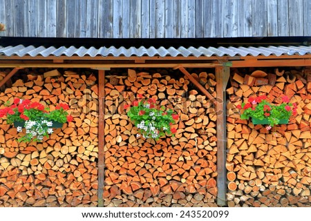 Chopped wood stack decorated with red and white flower pots, Tirol, Austria