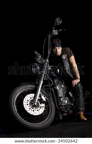 Chopper motorcycle front isolated on black and a rider man on it - stock photo